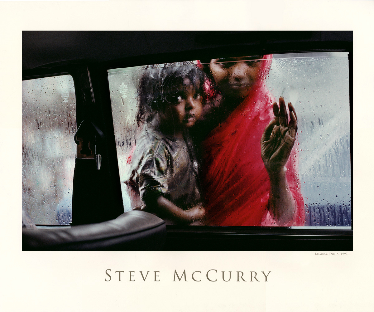 A mother and child beg for alms through a taxi window during the monsoon, Bombay, India, 1993.